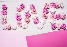 Rosas de papel de cores diferentes, apresentadas no amor da palavra um fundo colorido, cartão do dia de Valentim Fotografia de Stock Royalty Free
