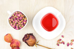 Rosas de té en una taza blanca, un té caliente y una flor color de rosa secada Fotos de archivo