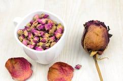 Rosas de té en una taza blanca y una flor color de rosa secada en la tabla de madera Fotos de archivo