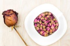 Rosas de té en una taza blanca y una flor color de rosa secada en la tabla de madera Imágenes de archivo libres de regalías