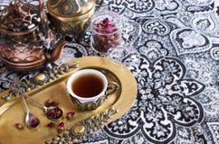 Rosas de té en una taza hermosa con adornos orientales Fotos de archivo libres de regalías