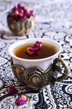 Rosas de té en una taza hermosa con adornos orientales Imágenes de archivo libres de regalías