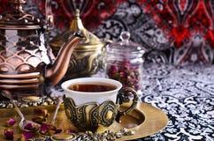 Rosas de té en una taza hermosa con adornos orientales Fotografía de archivo libre de regalías