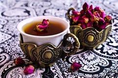 Rosas de té en una taza hermosa con adornos orientales Foto de archivo