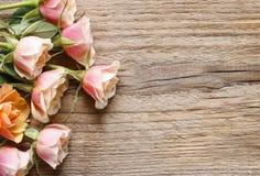 Rosas del rosa en colores pastel en fondo de madera Foto de archivo
