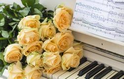 Rosas do pêssego no piano fotos de stock royalty free