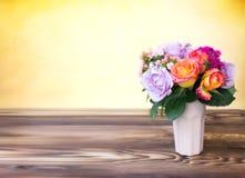 Rosas do ramalhete no vaso no fundo empy do espaço da tabela de madeira Imagem de Stock