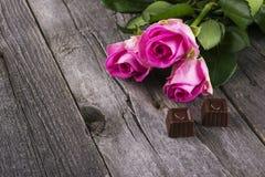Rosas e chocolates cor-de-rosa no formulário do coração contra um backgr escuro Foto de Stock