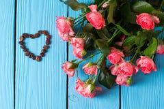 Rosas e coração em um fundo de madeira azul fotos de stock