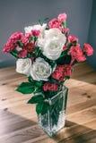 Rosas e cravos-da-índia no vaso de vidro Fotos de Stock