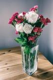 Rosas e cravos-da-índia no vaso de vidro Imagem de Stock