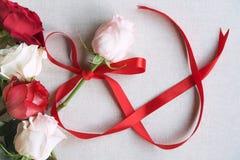 Rosas e fita vermelha na forma da infinidade Fotografia de Stock Royalty Free