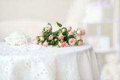 Rosas e grânulos cor-de-rosa delicados da pérola na tabela Foto de Stock