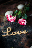 Rosas e mensagem agradáveis do amor no fundo rústico Imagem de Stock