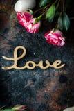 Rosas e mensagem agradáveis do amor no fundo rústico Imagem de Stock Royalty Free