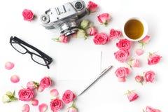 Rosas e nota do rosa da câmera do vintage no fundo branco Configuração lisa Vista superior imagem de stock