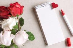 Rosas e um caderno espiral vazio com coração Foto de Stock Royalty Free