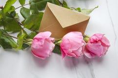 Rosas e um envelope do ofício como um símbolo do dia de Valentim imagem de stock