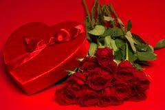 Rosas e uma caixa vermelha do coração em um fundo vermelho Fotos de Stock Royalty Free