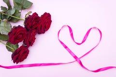 Rosas em um fundo cor-de-rosa, um ramalhete de rosas vermelhas O dia de Valentim, o dia de mãe feliz Dia feliz do ` s das mulhere fotos de stock