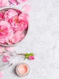 Rosas en cuenco gris con la botella del agua, poner crema y rosada con la cabina Imagenes de archivo