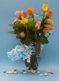 Rosas en el florero de cristal con las cintas azules y los corazones Imagenes de archivo