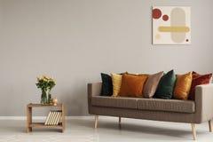 Rosas en florero en estante de madera con los libros al lado del sofá cómodo con las almohadas verdes de la naranja, amarillas, b fotografía de archivo libre de regalías
