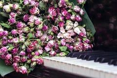 Rosas en piano Foto de archivo libre de regalías