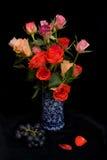Rosas en un florero azul. Imagen de archivo