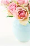 Rosas en un florero azul claro en el fondo elegante lamentable beige poner crema Foto de archivo libre de regalías
