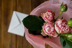 Rosas en un florero con el sobre en fondo gris de madera foto de archivo libre de regalías