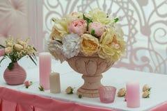 Rosas en un florero y velas en la tabla Imagen de archivo