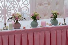 Rosas en un florero y velas en la tabla Foto de archivo