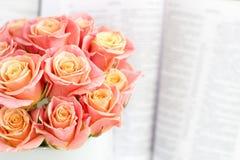 Rosas en una caja redonda y la biblia Rosas rosadas hermosas en un fondo de madera blanco Rosas rosadas hermosas y la biblia Foto de archivo