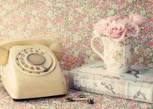 Rosas en una taza y un teléfono de café Imágenes de archivo libres de regalías
