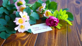 Rosas florecientes hermosas y una tarjeta de felicitación para la madre