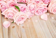 Rosas florecientes rosadas en la madera Foto de archivo libre de regalías