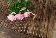 Rosas florecientes rosadas en la madera Foto de archivo