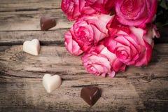 Rosas frescas e corações cor-de-rosa do chocolate na madeira Imagens de Stock