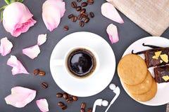 Rosas, galletas y taza de café en fondo negro Endecha plana imágenes de archivo libres de regalías