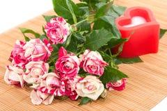 Rosas hermosas y vela roja en la forma de un corazón. Foto de archivo