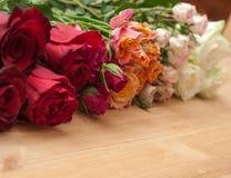 Rosas na ordem do inclinação no fundo de madeira imagem de stock royalty free