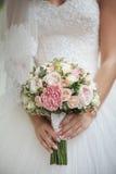Rosas nas mãos da noiva Foco em flores Imagens de Stock Royalty Free