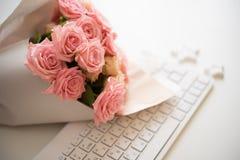 Rosas no teclado de computador branco foto de stock