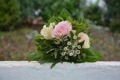 Rosas - o ramalhete encontra-se na parede branca na natureza Fotografia de Stock Royalty Free