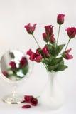 Rosas púrpuras en un florero con el espejo Fotos de archivo