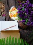 Rosas púrpuras y amarillas artificiales con un cuaderno abierto Imagen de archivo libre de regalías