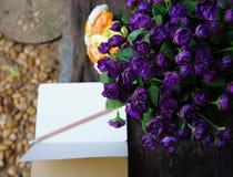 Rosas púrpuras y amarillas artificiales con un cuaderno abierto Fotografía de archivo libre de regalías