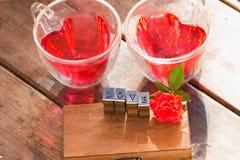 Rosas para la tarjeta del día de San Valentín, el agua roja en taza del corazón y el mensaje del amor Foto de archivo