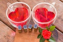 Rosas para la tarjeta del día de San Valentín, el agua roja en taza del corazón y el mensaje del amor Imagen de archivo